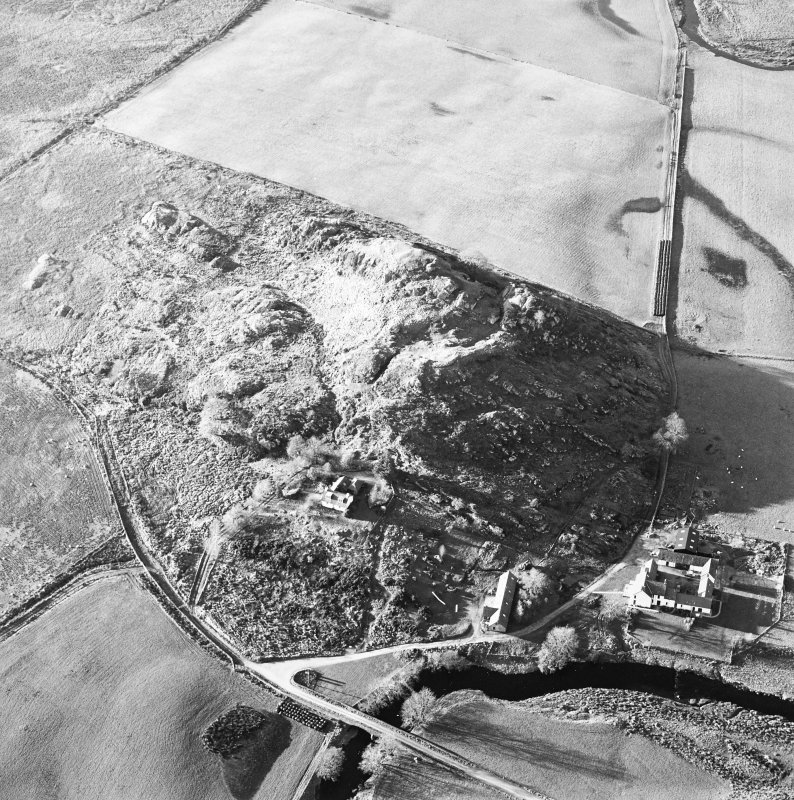 Oblique aerial view centred on the remains of the fort with the farmstead adjacent, taken from the ESE.