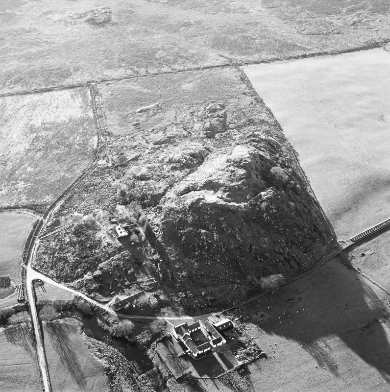 Oblique aerial view centred on the remains of the fort with the farmstead adjacent, taken from the ENE.