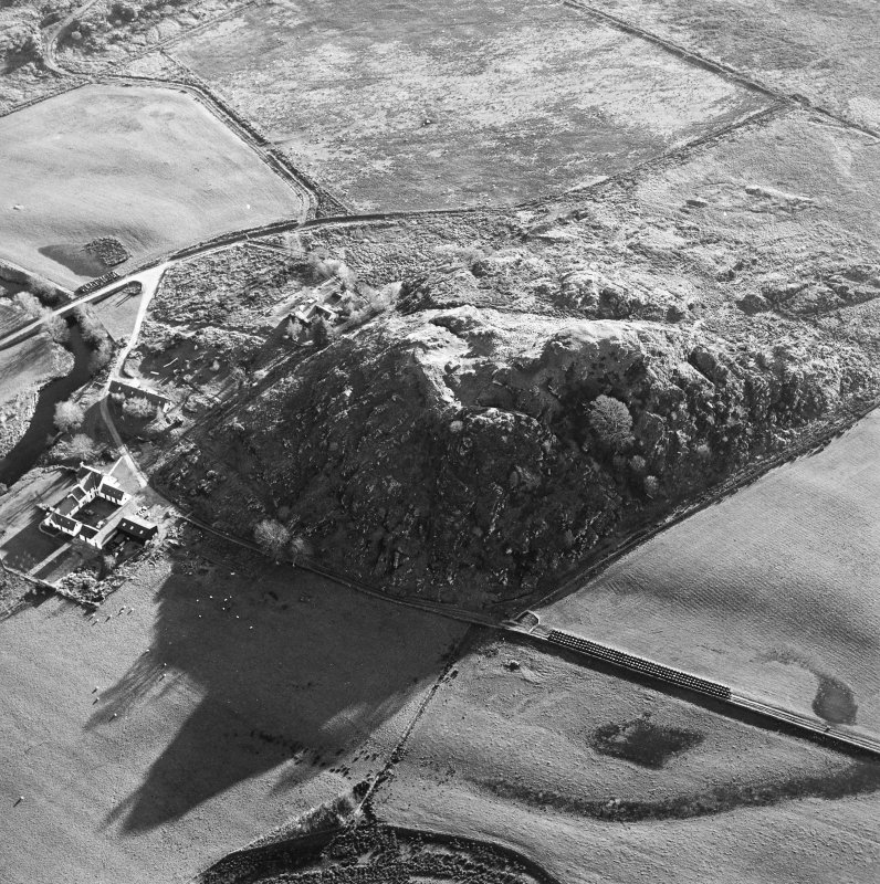 Oblique aerial view centred on the remains of the fort with the farmstead adjacent, taken from the N.