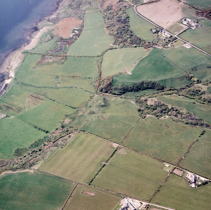 Oblique aerial view centred on the remains of the dun with the township adjacent, taken from the ESE.