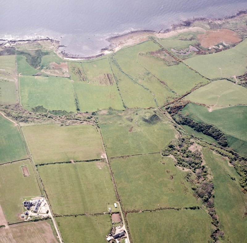 Oblique aerial view centred on the remains of the dun, taken from the ENE.
