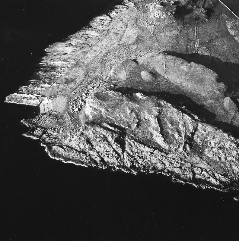 Oblique aerial view of Dunagoil (centre) showing cultivation remains, cist, and field boundaries, taken from SW.