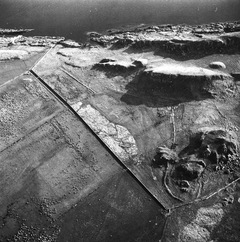 Oblique aerial view showing forts, cist (at centre right), cultivation remains and field clearance cairns, taken from N.