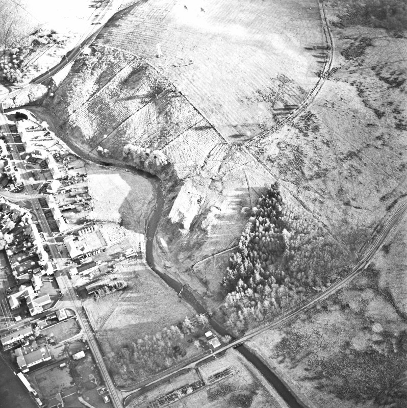 Oblique aerial view centred on the remains of the coal mine with the enclosure adjacent, taken from the N.