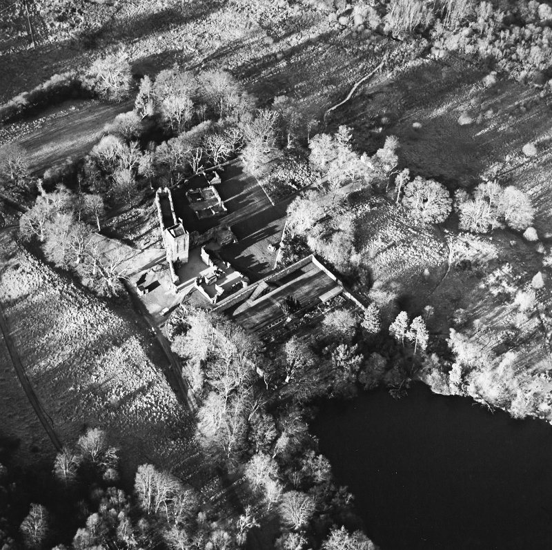 Oblique aerial view centred on the remains of the castle, chapel and tower, taken from the SE.