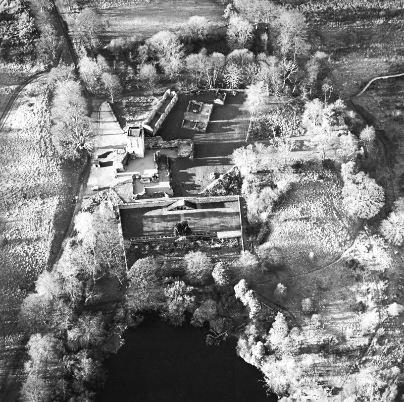 Oblique aerial view centred on the remains of the castle, chapel and tower, taken from the E.