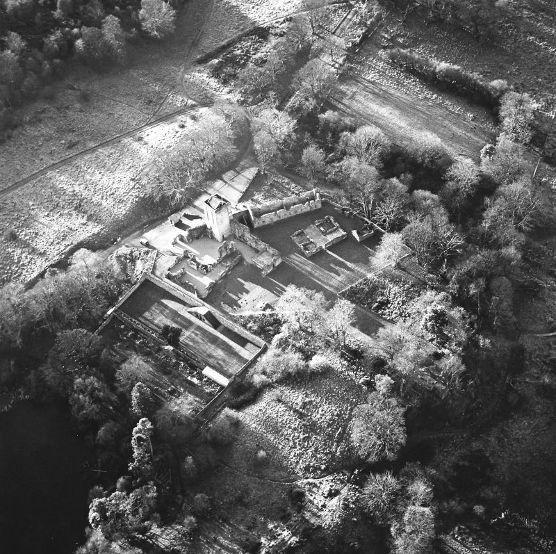 Oblique aerial view centred on the remains of the castle, chapel and tower, taken from the NE.