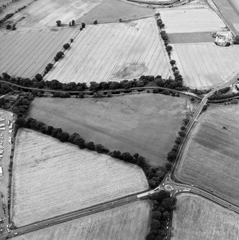 Oblique aerial view centred on the cropmarks of the Antonine Wall near Cadder, taken from the SE.