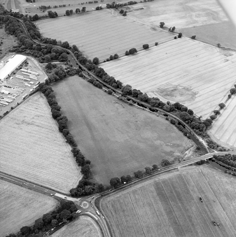 Oblique aerial view centred on the cropmarks of the Antonine Wall near Cadder, taken from the ESE.