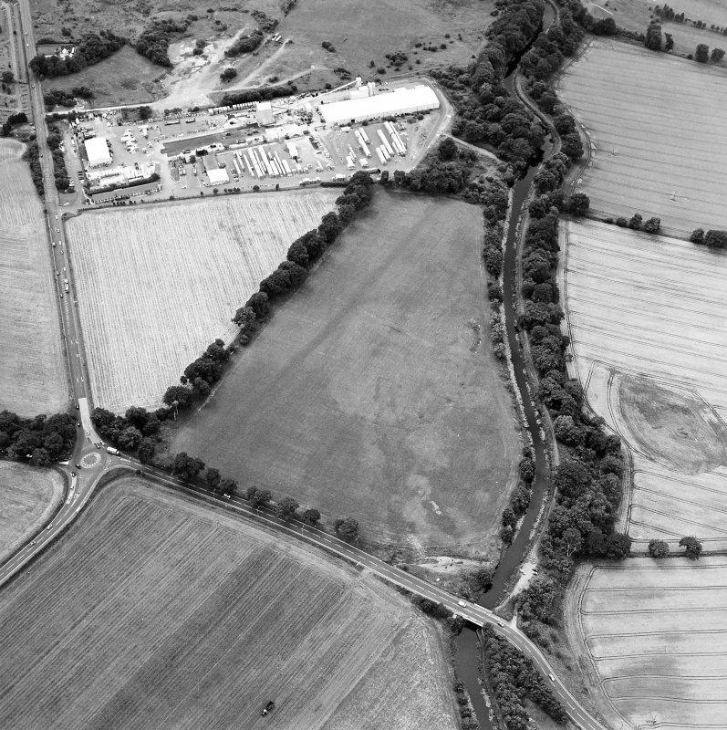 Oblique aerial view centred on the cropmarks of the Antonine Wall near Cadder, taken from the NE.
