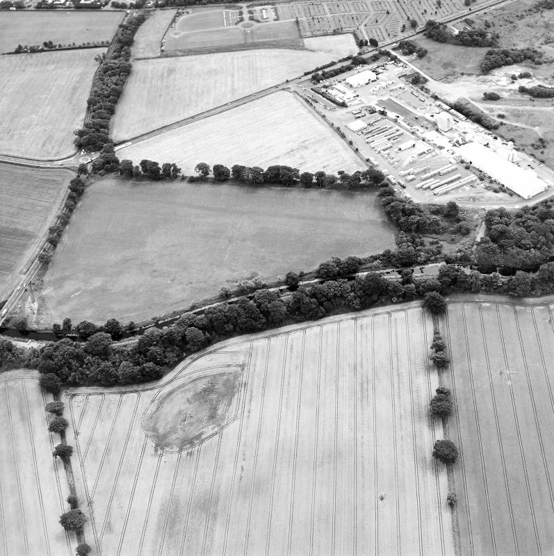Oblique aerial view centred on the cropmarks of the Antonine Wall near Cadder, taken from the NNW.