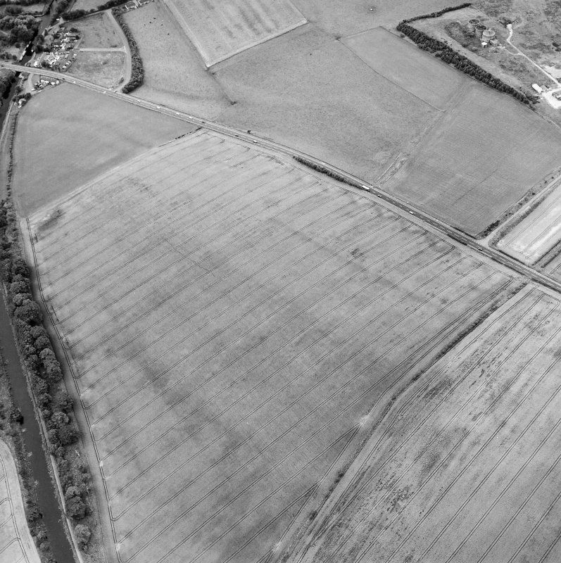 Oblique aerial view centred on the cropmarks of the Antonine Wall and the site of the Roman fortlet, taken from the SE.