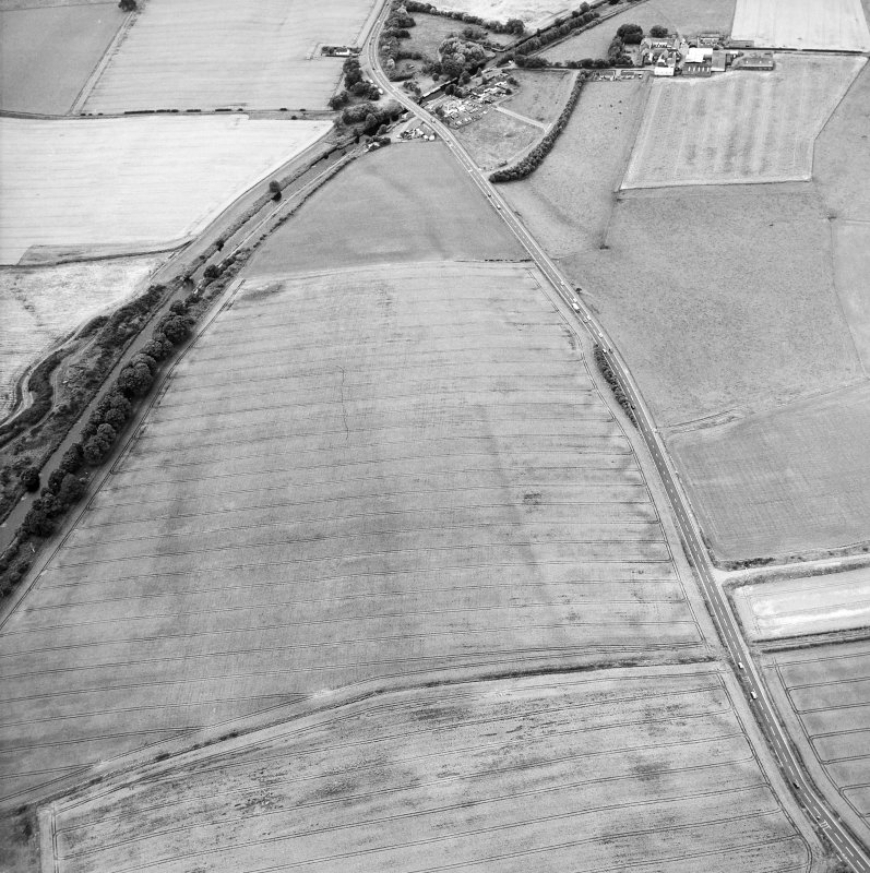 Oblique aerial view centred on the cropmarks of the Antonine Wall and the site of the Roman fortlet, taken from the ENE.