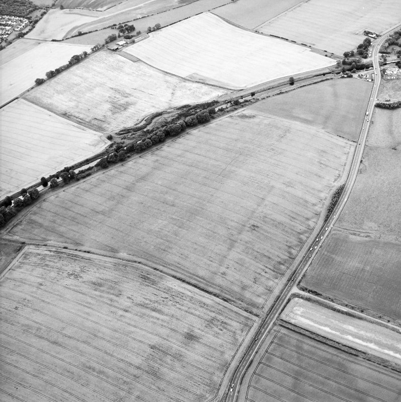 Oblique aerial view centred on the cropmarks of the Antonine Wall and the site of the Roman fortlet, taken from the NE.