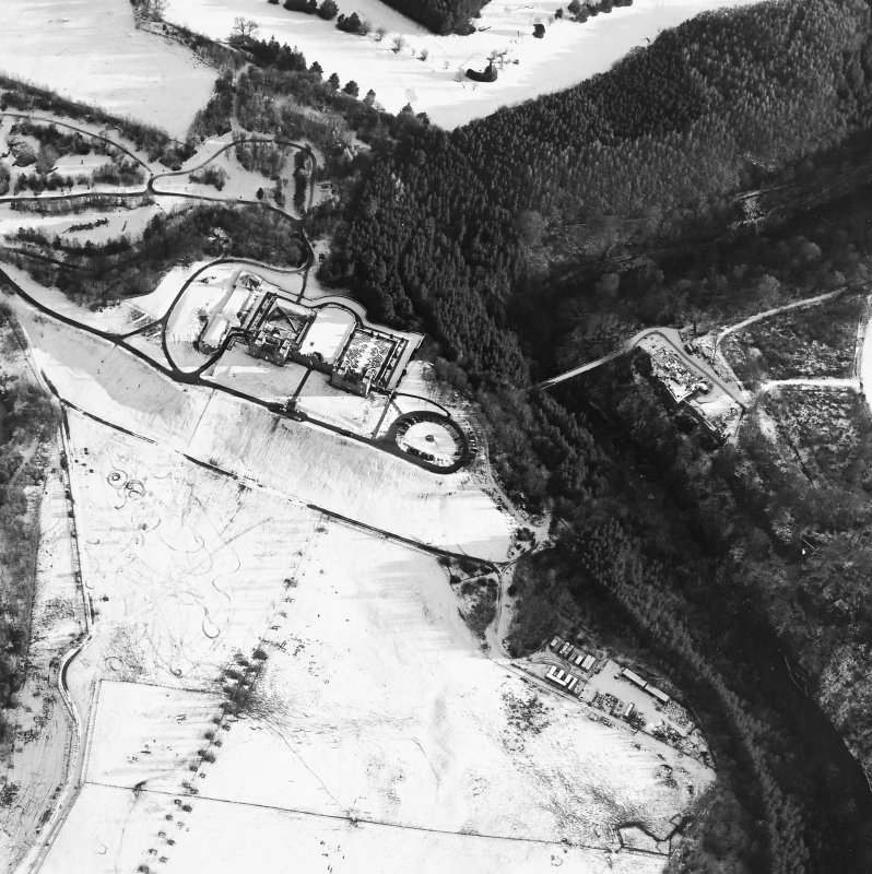 Oblique aerial view centred on the hunting lodge and ornamental gardens with the remains of a castle adjacent, taken from the NW.