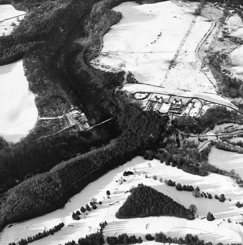 Oblique aerial view centred on the hunting lodge and ornamental gardens with the remains of a castle adjacent, taken from the SE.