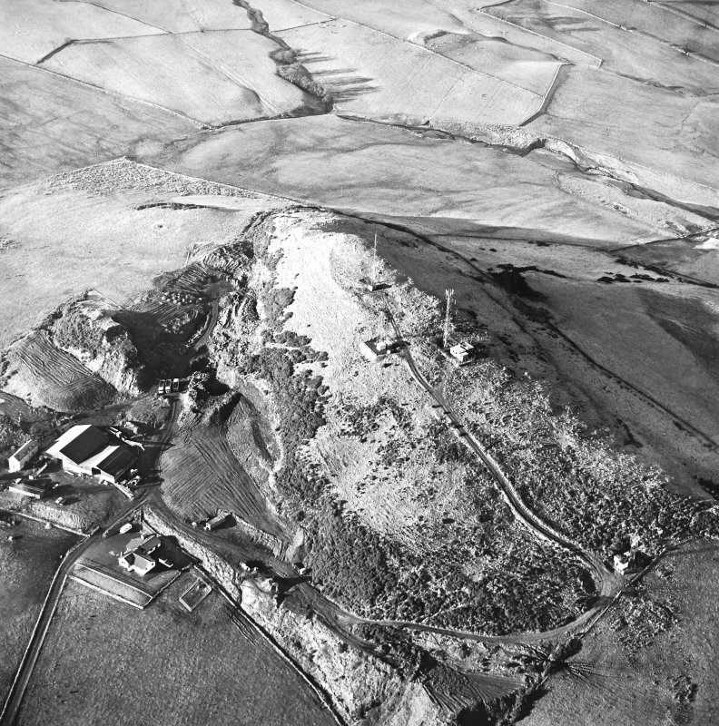Oblique aerial view centred on the radio station and the remains of the fort with the quarry adjacent, taken from the SE.