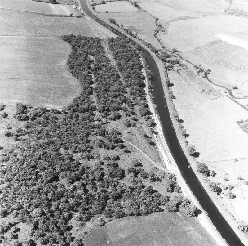 Oblique aerial view of the Antonine Wall and the site of the fortlet at Seabegs Wood from the east, centred c. NS 8139 7931.