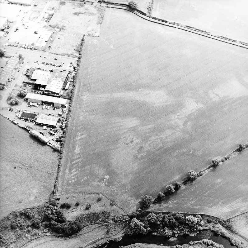Oblique aerial view centred on the cropmarks of the pits, rig and Roman temporary camps, taken from the WNW.