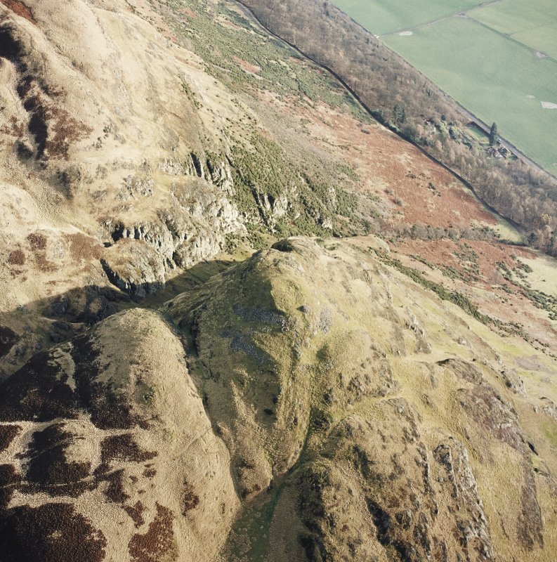 Oblique aerial view of Dumyat centred on the remains of a fort and cairn, taken from the WNW.