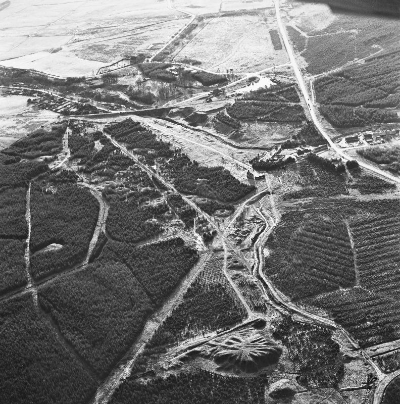 Wilsontown, oblique aerial view, taken from the NE, showing the bings of two coal mines at the bottom, and the remains of ironworks, workers' rows, lime kilns, coke ovens and buildings across the remainder of the photograph.