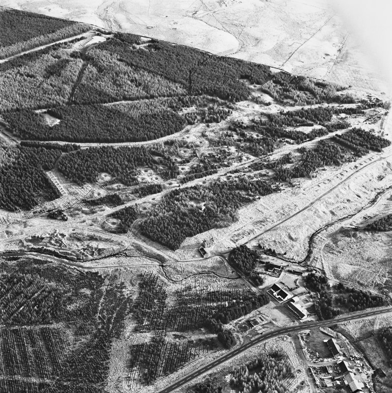 Wilsontown, oblique aerial view, taken from the ESE, showing the remains of workers' rows in the centre left of the photograph, and the ruins of the public house and shop, and a large area of bell pits, in the centre.