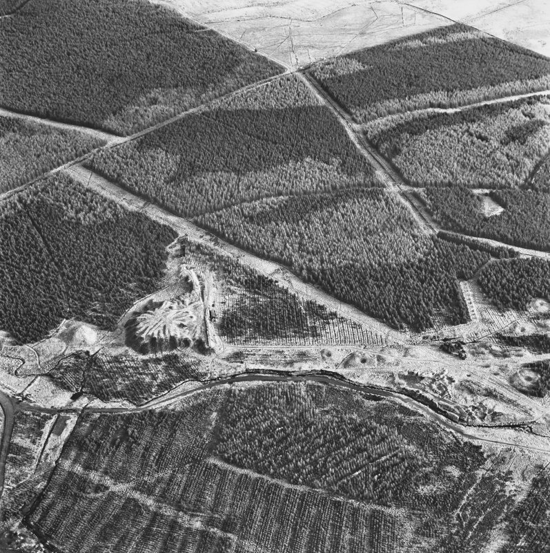 Wilsontown, oblique aerial view, taken from the E, showing the bings of two coal mines in the centre left of the photograph, and the remains of a workers' row, and an area of bell pits, in the centre right.