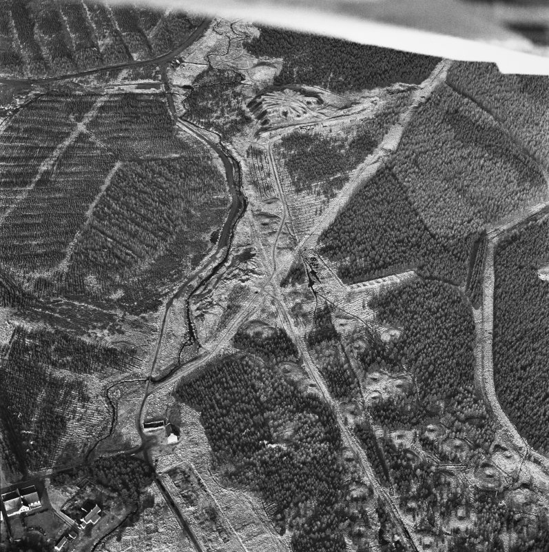 Wilsontown, oblique aerial view, taken from the SSW, showing the bings of two coal mines at the top of the photograph, and the remains of workers' rows, buildings  and bell pits in the bottom half.