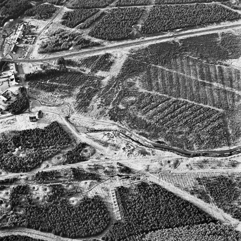 Wilsontown, oblique aerial view, taken from the E, showing the the remains of workers' rows and buildings, and bell pits, across the bottom half of the photograph.