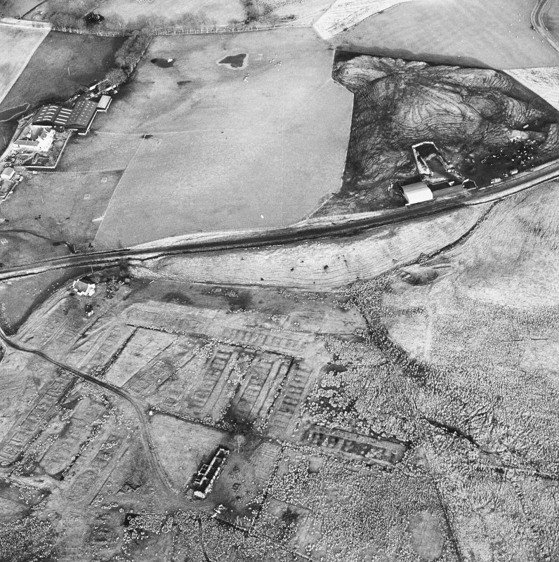 Haywood, oblique aerial view, taken from the SW, showing Haywood village with the remains of miners' rows and a farmstead in the bottom left-hand corner of the photograph, and a cottage and the two bings of a coal mine adjacent to the dismantled railway in the top right-hand corner.