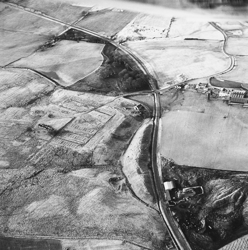 Haywood, Droveloan and Greenbank, oblique aerial view, taken from the ESE, showing Haywood village with the remains of miners' rows and a farmstead in the centre of the photograph, a cottage and the two bings of a coal mine adjacent to the dismantled railway, and Droveloan cottage, in the bottom right-hand corner, and an area of rig at Greenbank in the centre right.