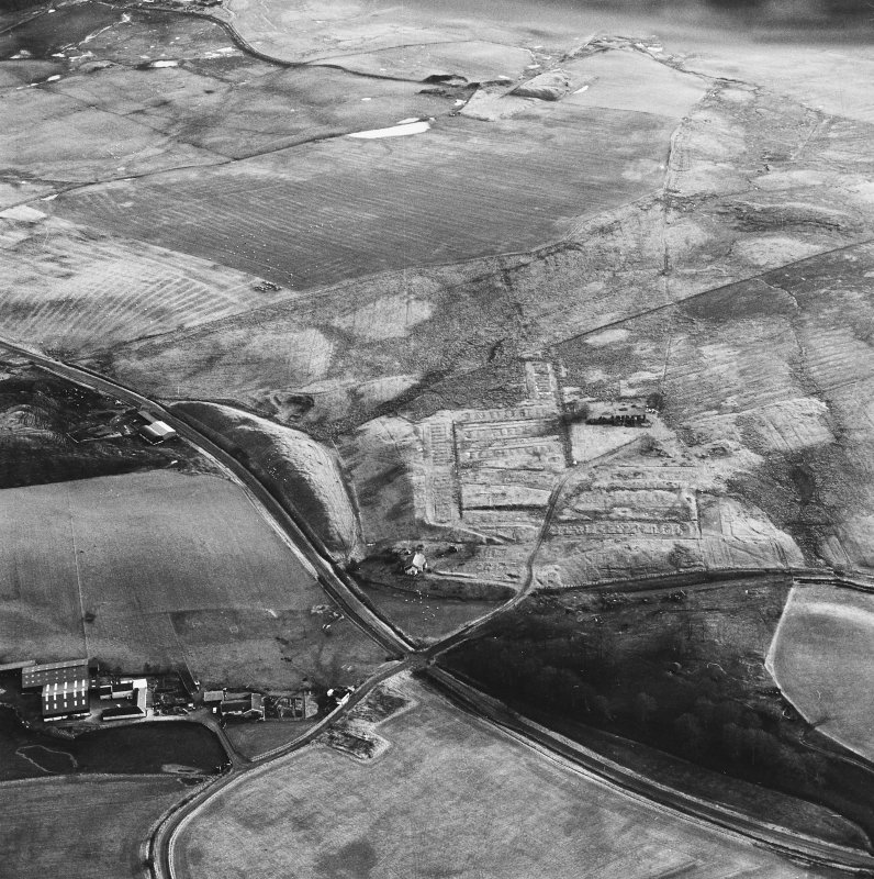 Haywood, Droveloan and Greenbank, oblique aerial view, taken from the NNW, showing Haywood village with the remains of miners' rows and a farmstead in the centre of the photograph, the two bings of a coal mine adjacent to the dismantled railway at the left edge, and areas of rig at Droveloan cottage in the top half, and Greenbank in the right centre.