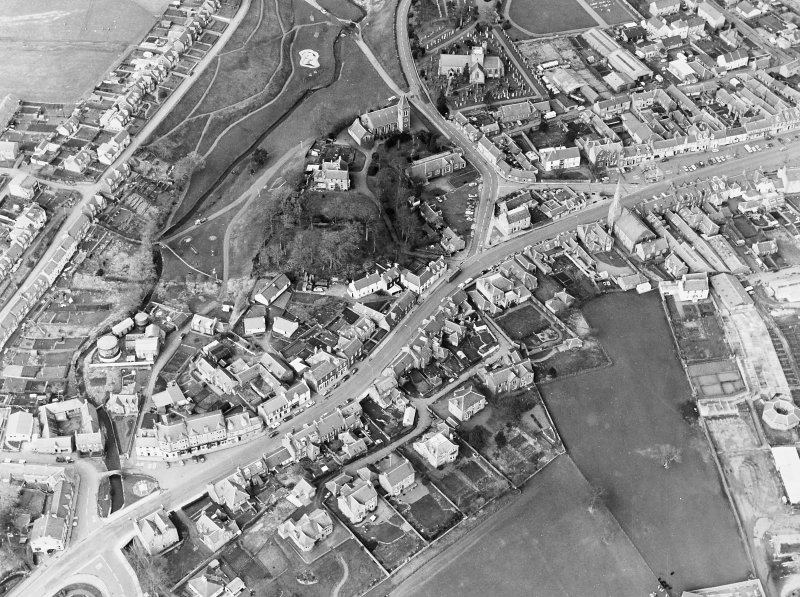 General oblique aerial view centred on the remains of the fort with the churches and churchyard adjacent, taken from the S.