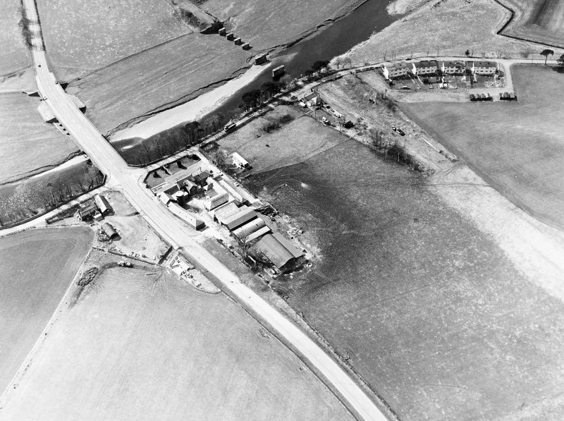 Oblique aerial view centred on the road bridge and the remains of the motte and railway viaduct, taken from the E.
