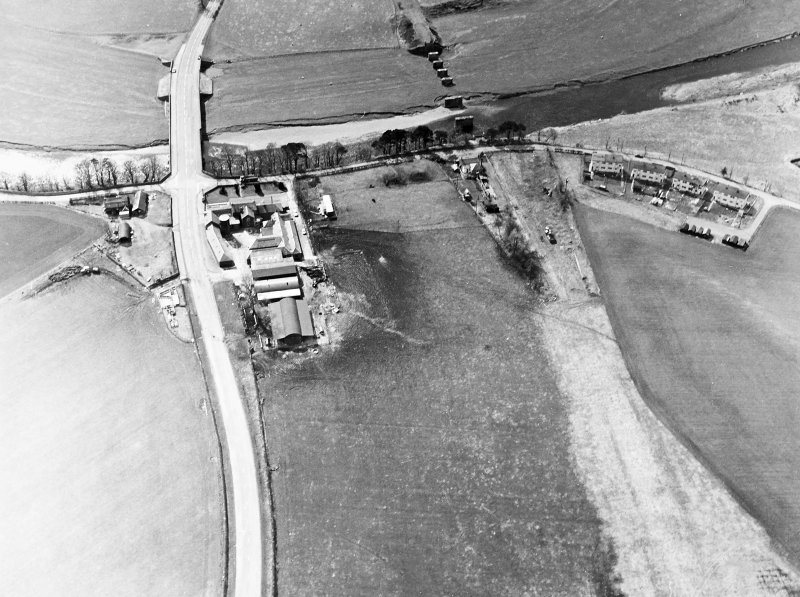 Oblique aerial view centred on the road bridge and the remains of the motte and railway viaduct, taken from the ENE.