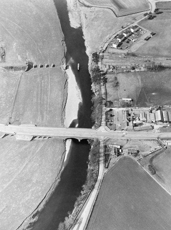 Oblique aerial view centred on the road bridge and the remains of the motte and railway viaduct, taken from the SE.