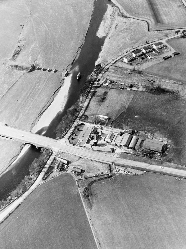 Oblique aerial view centred on the road bridge and the remains of the motte and railway viaduct, taken from the ESE.
