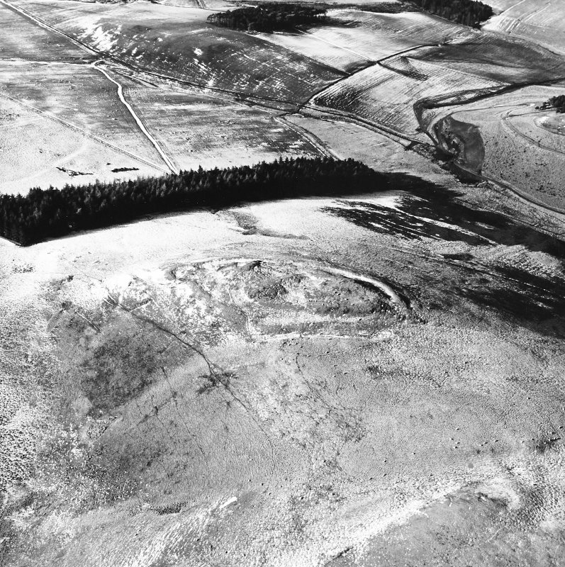 Snaip Hill, oblique aerial view, taken from the NE, centred on the remains of fort, with an enclosure and possible hut circle.