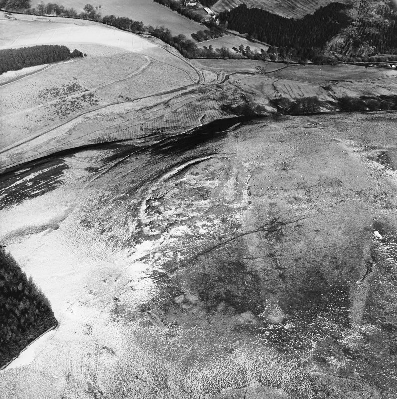 Snaip Hill, oblique aerial view, taken from the S, centred on the remains of fort, with an enclosure and possible hut circle to the right of the photograph.