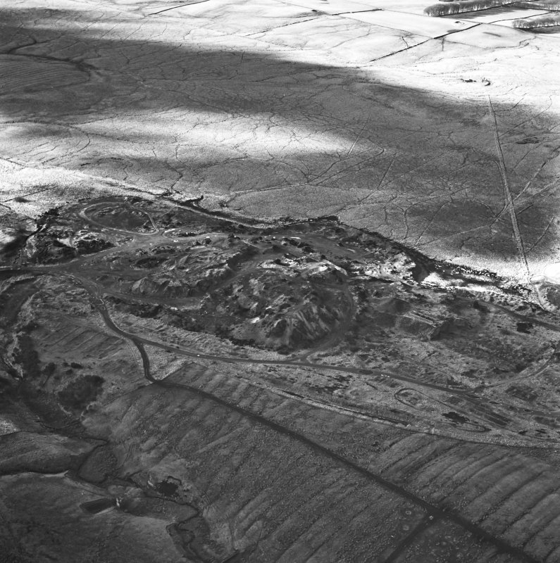 Tarbrax Shale-Oil Works, oblique aerial view, taken from the E, showing one massive bing of the shale-oil mine alongside a tramway in the centre of the photograph, with another tramway running up the right-hand side, and the remains of an engine house and dam, and an area of rig, at the bottom.