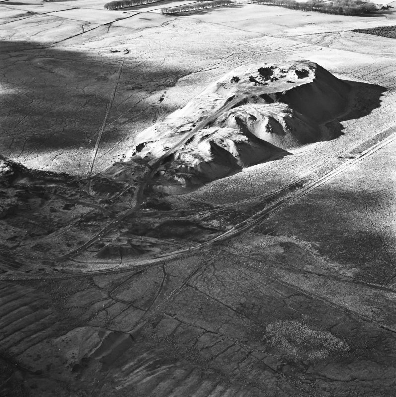 Tarbrax Shale-Oil Works, oblique aerial view, taken from the ENE, showing the massive bing of the shale-oil mine in the top half of the photograph, between a tramway, on the left, and the Tarbrax Branch of the Caledonian Railway on the right. A further shale bing is visible in the bottom half, overlying an area of rig.