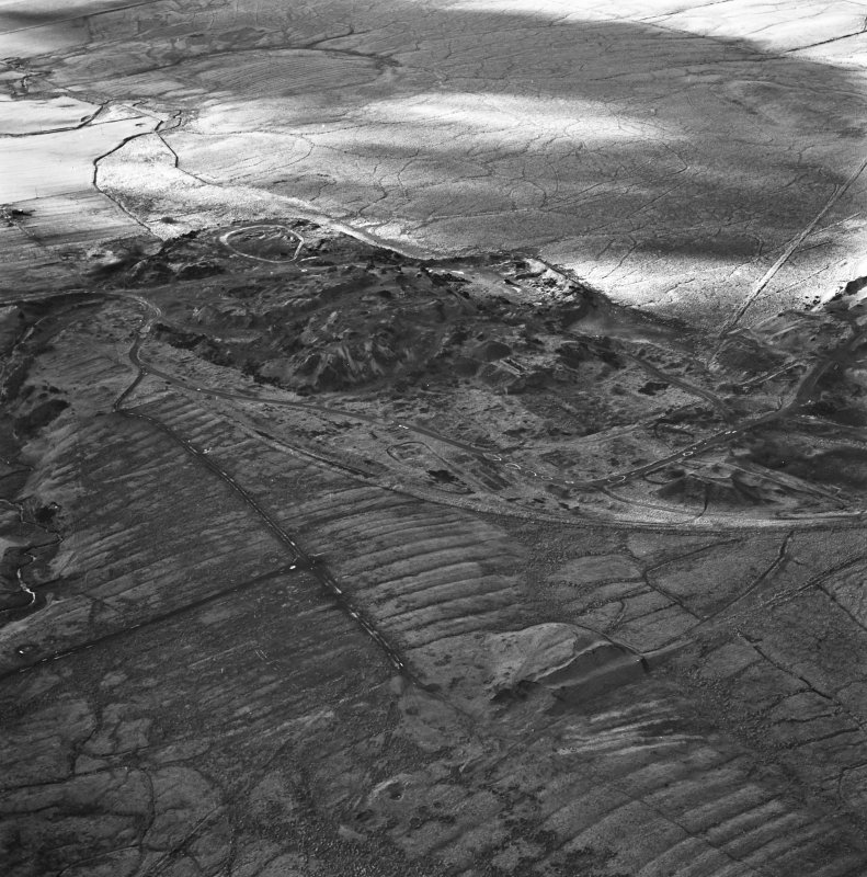 Tarbrax Shale-Oil Works, oblique aerial view, taken from the NE, showing one massive bing of the shale-oil mine in the centre of the photograph, with a tramway running off into the top right-hand corner, and the Tarbrax Branch of the Caledonian Railway running alongside it. A further shale bing, and the ruins of an engine house and dam, are visible in the bottom half, overlying an area of rig.