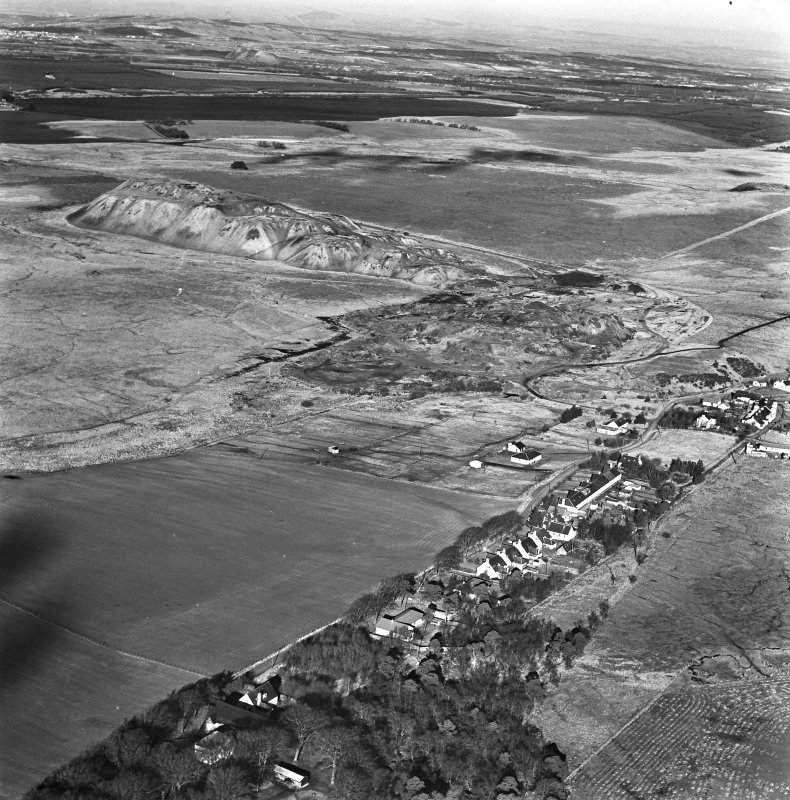 Tarbrax Shale-Oil Works, oblique aerial view, taken from the SSE, showing Tarbrax village in the foreground, and the massive bings and tramways of the shale-oil mine in the centre of the photograph. Two area of rig, Greenfield Burn, and Lawhead, are visible in the bottom left-hand and right-hand corners respectively. Tarbrax Church is amongst a group of buildings in the left centre.