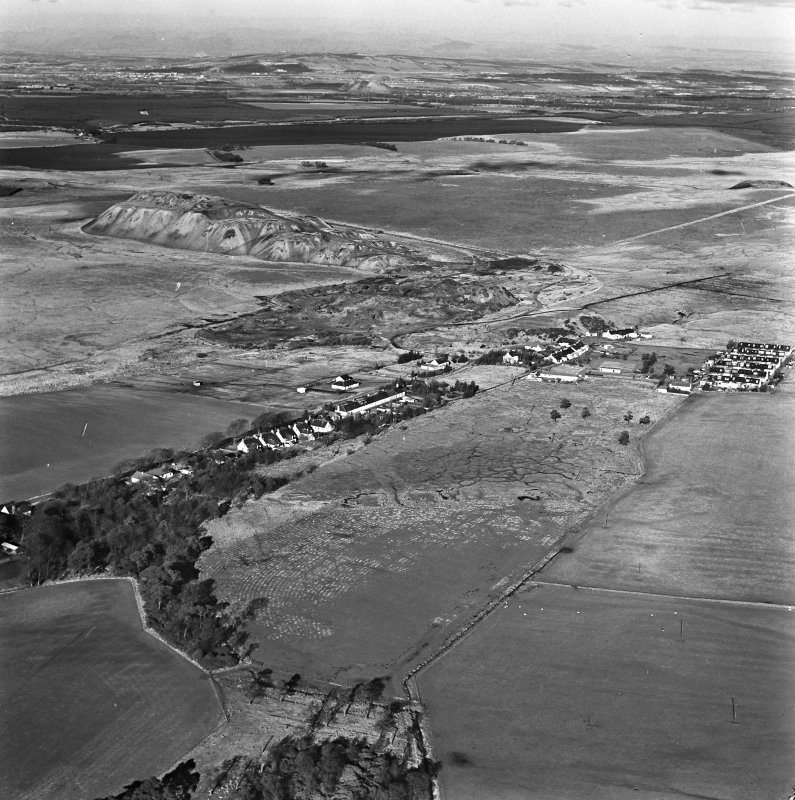 Tarbrax Shale-Oil Works, oblique aerial view, taken from the S, showing Tarbrax village and the massive bings and tramways of the shale-oil mine in the centre and top half of the photograph. Two area of rig, Greenfield Burn, and Lawhead, are visible in the bottom left-hand and right-hand corners respectively. Tarbrax Church is amongst a group of buildings in the centre of the photograph.