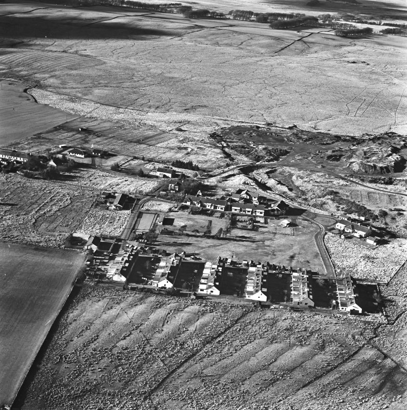 Tarbrax Shale-Oil Works, oblique aerial view, taken from the E, showing Tarbrax village in the centre of the photograph, and part of one of the bings of the shale-oil mine in the centre right.. An area of rig is visible at the bottom.