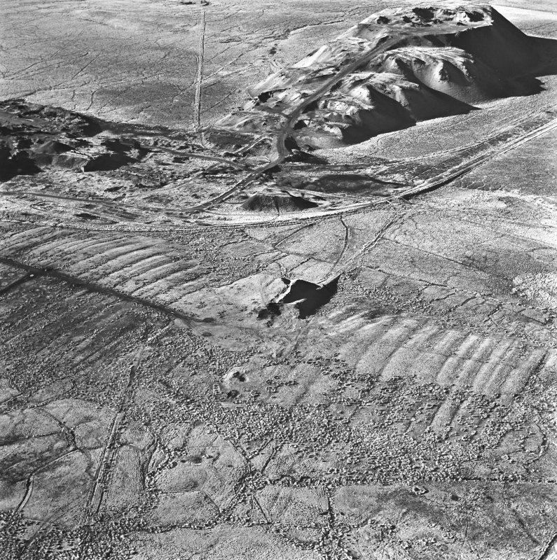 Tarbrax Shale-Oil Works, oblique aerial view, taken from the ENE, showing one of the massive shale bings associated with the shale-oil mine at the top of the photograph, with a tramway running alongside it to the left, and the Tarbrax Branch of the Caledonian Railway to the right. A second, smaller, shale bing overlies an area of rig in the bottom half.
