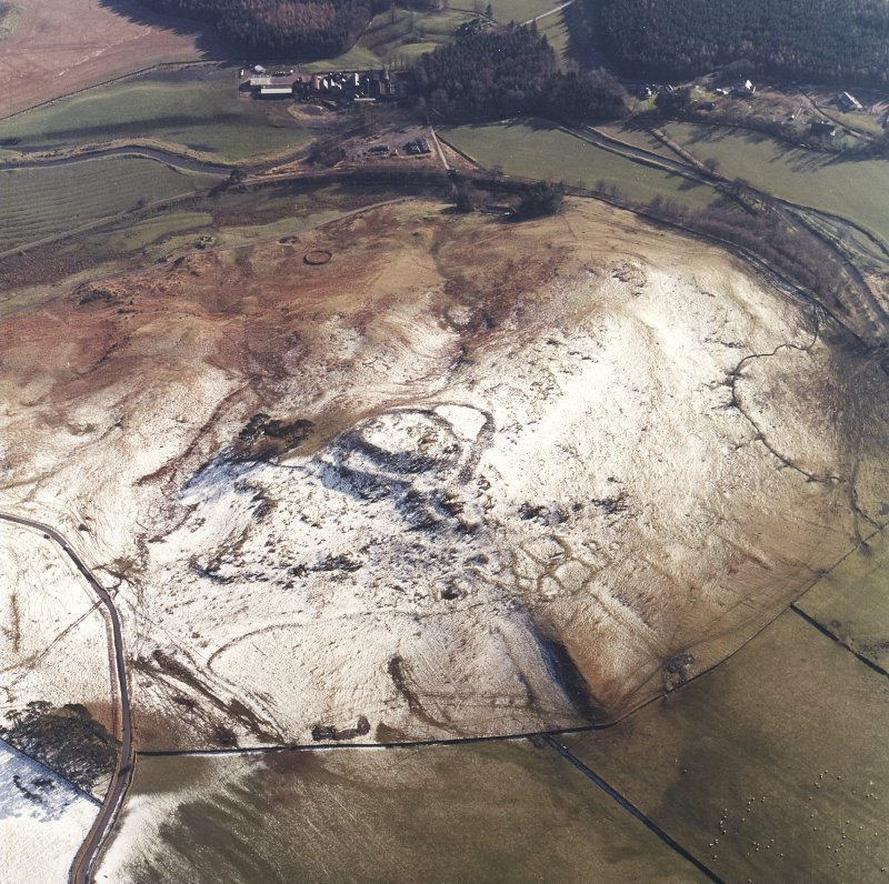 Oblique aerial view centred on the remains of the fort, settlements and field system with the farmsteading adjacent, taken from the N.