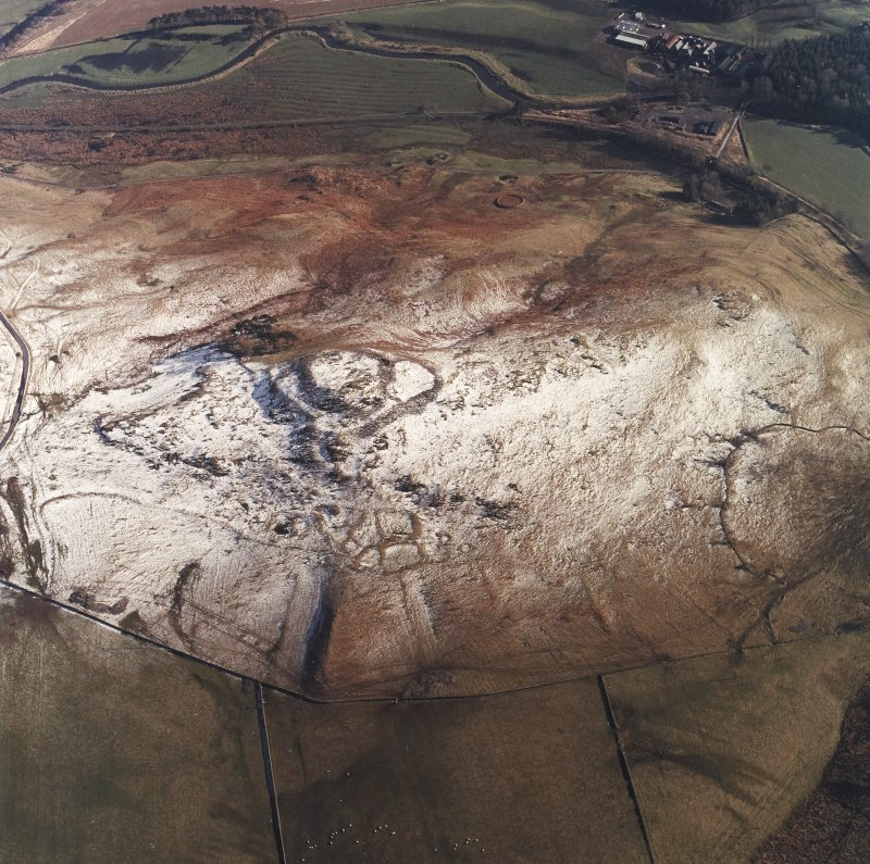 Oblique aerial view centred on the remains of the fort, settlements and field system with the farmsteading adjacent, taken from the NW.