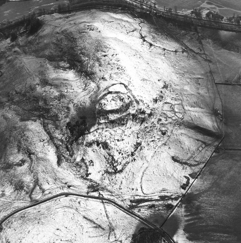 Oblique aerial view centred on the remains of the fort, settlements and field system, taken from the NE.