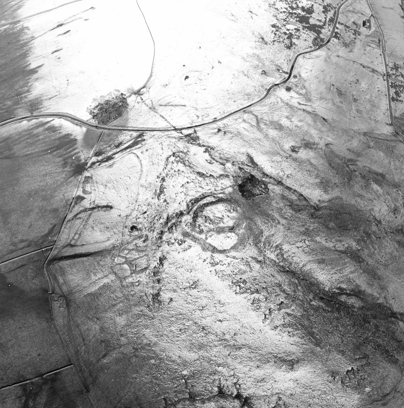 Oblique aerial view centred on the remains of the fort, settlements and field system, taken from the SW.
